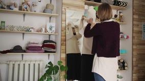 För hattframdel för ung kvinna montering stucken spegel för längd full i boutique arkivfilmer