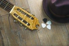 För hattgitarr för akustisk gitarr hacka på träbakgrund arkivfoto