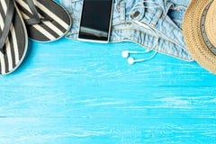 För hatthäftklammermatare för ram eleganta hörlurar för smartphone för jeans på blå träbakgrund, copyspace för text, sommarsemest royaltyfri foto