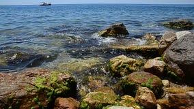 för havsseascape för blåa rocks sommar för sky Stenig strand av azurt vatten av havet eller havet I bakgrunden seglar ett nöjefar stock video