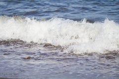 För havsvatten för förkylning blå bränning över kusten Kyliga havsvågfärgstänk över kust Arkivfoto