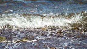 För havsvatten för förkylning blå bränning över kusten Kyliga havsvågfärgstänk över kust Arkivbild