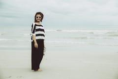 För hipsterindy för stående ensam ställning för asiatisk enkel kvinnor solglasögon för kläder bara på stranden royaltyfria foton