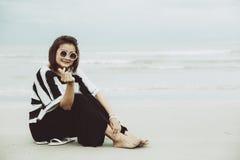 För hipsterindy för stående som asiatisk enkel solglasögon för kläder kvinnor placerar på stranden fotografering för bildbyråer