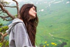 För hipsterkvinna för stående nätt sammanträde på bergöverkant Arkivbild