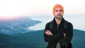 För hipsterman för stående europeiskt vänligt anseende på bergöverkant på solnedgången stock video