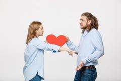 För hjärtaform för par hållande papper med ilsket ansiktsuttryck mot grå färger arkivbilder