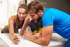 För idrottshallkläder för par bärande läs- meddelande på mobiltelefonen Arkivbilder