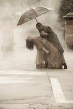 För indier för påkläddpar smartly dans under ett paraply i regnet arkivbilder