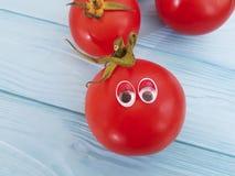 För ingrediensbegreppet för tomaten synar den roliga organiska personen tecknade filmen på blå träpositiv sinnesrörelse Arkivbild
