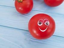 För ingrediensnaturen för tomaten synar den roliga organiska personen för begreppet tecknade filmen på blå träpositiv sinnesrörel Royaltyfri Fotografi