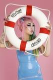 För innehavflöte för ung kvinna rör över rosa bakgrund Fotografering för Bildbyråer
