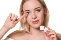 För innehavkontakt för ung kvinna fall och lins för linser framme av hennes framsida på vit bakgrund royaltyfri fotografi