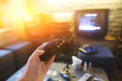 För innehavlek för ung man som en kontrollant spelar videospel Oldschool konsol Dobbelbegrepp Royaltyfria Bilder