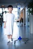 För iv-droppande för pojke tålmodig hållande intravenös ställning i korridor royaltyfri bild
