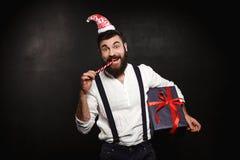 För julgåva för ung stilig man hållande ask över svart bakgrund arkivfoto