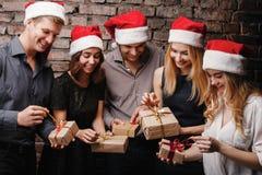 För julgåva för lyckligt folk öppnande askar royaltyfri fotografi