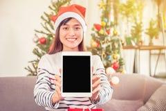 För julhatt för kvinna bärande dator för minnestavla hållande arkivfoto