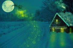 För jullandskap för hus snöig träd för gran på natten och den stora månen Royaltyfria Bilder