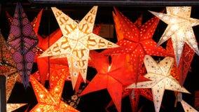 För julstjärnor för härligt dekorativt papper glödande ljus på julmarknad i Tyskland lager videofilmer