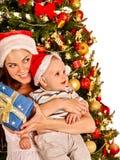 För jultomtenhatten för mamman behandla som ett barn det bärande innehavet under Royaltyfri Bild
