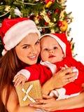 För jultomtenhatten för mamman behandla som ett barn det bärande innehavet under Fotografering för Bildbyråer