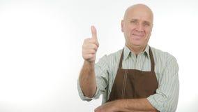 För kökförkläde för lycklig person bärande tummar upp bra jobbtecken royaltyfri foto
