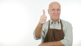 För kökförkläde för lycklig person bärande tummar upp bra jobbtecken royaltyfri fotografi