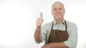 För kökförkläde för lycklig person bärande tummar upp bra jobbtecken arkivfoton