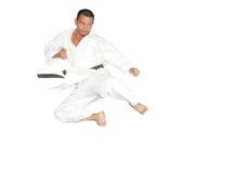 För karateman för svart bälte banhoppning som ger en hög spark Royaltyfri Bild