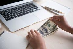För kassa händer in Vinster besparingar Bunt av dollar Arkivbild