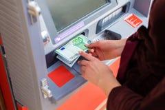 För kassa pengar ut på en ATM Royaltyfri Bild