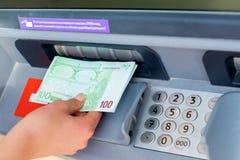 För kassa pengar ut på en ATM Royaltyfri Foto