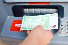 För kassa pengar ut på en ATM Royaltyfria Bilder