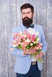 För klädersmoking för man väl ansad bukett för blommor för håll för fluga Invitera henne som daterar Romantisk man med blommor Ro fotografering för bildbyråer