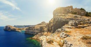 För klippasikt för sommar nedersta akropol av Lindos av Rhodes med dramatisk himmelbakgrund Arkivbilder