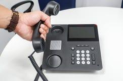 För klockahåll för affärsman bärande telefonlur av IP-telefonen på tabellen med den vänstra handen för att kalla ut Arkivbild