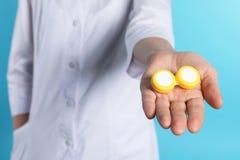 För kontaktlins för kvinnlig doktor hållande fall royaltyfri foto