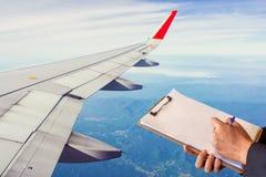 För kontrollinnehav för man som plan skrivplatta skriver anmärkningsnotepaden på himmel royaltyfri fotografi