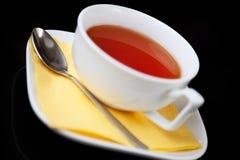 för koppsked för bakgrund svart tea Arkivfoto