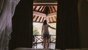 För kvinnaöppning för tillbaka sikt lyckliga unga turist- gardiner för chalet och fönsterdörr som ut går för att sträcka på den s lager videofilmer