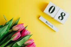 8 för kvinna` s för mars lyckligt begrepp för dag Med trätulpan för kvarterkalender och rosa färgpå gul bakgrund kopiera avstånd Arkivfoton