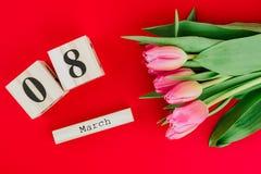 8 för kvinna` s för mars lyckligt begrepp för dag Med trätulpan för kvarterkalender och rosa färgpå röd bakgrund kopiera avstånd Royaltyfri Foto