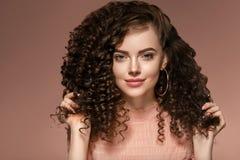 För kvinnafrisyr för lockigt hår dam med långt brunetthår fotografering för bildbyråer