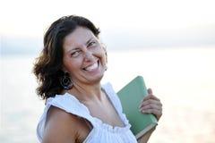 För kvinnainnehav för lycklig attraktiv 40-tal mogen smi för bok Royaltyfri Bild