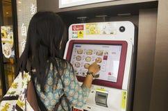 För kvinnaköpande för handelsresande thai ramen från varuautomaten på nudeln Royaltyfri Fotografi