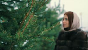 För kvinnamidja för brunett rikt lag av brun päls nära julgranultrarapid stock video