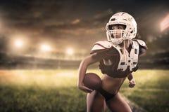 För kvinnaspelare för amerikansk fotboll boll för innehav på stadionpanoramasikten royaltyfri foto