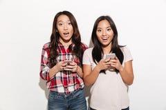 För kvinnasystrar för asiat förvånat prata royaltyfri bild