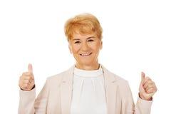 För kvinnavisning för leende elegant hög tumme upp Fotografering för Bildbyråer